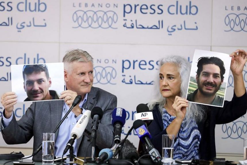 Marc (left) and Debra Tice, parents of US journalist Austin Tice who was kidnapped in Syria five years prior, hold respective dated portraits of him during a press conference in the Lebanese capital Beirut on July 20, 2017.