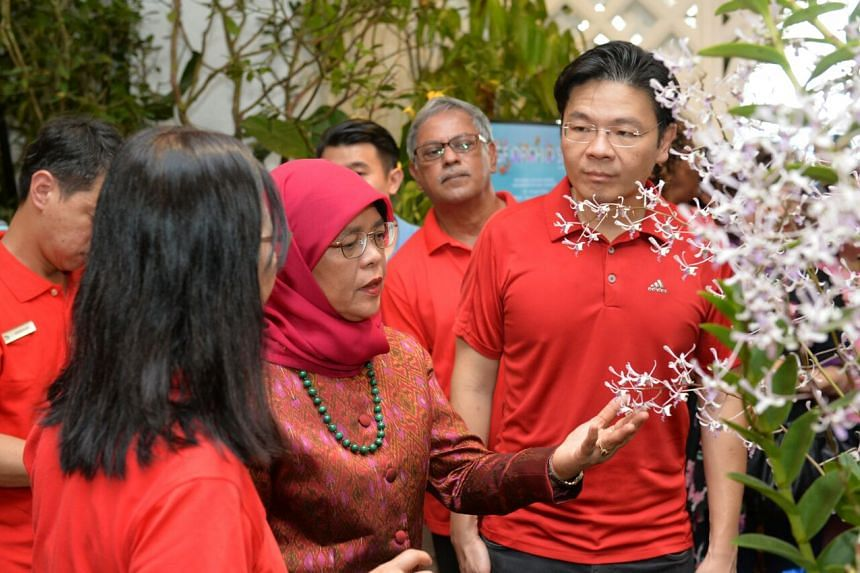 President Halimah Yacob (centre) and National Development Minister Lawrence Wong (right) at the opening of the inaugural Singapore Garden Festival Orchid Show at the Botanic Gardens, on April 21, 2018.