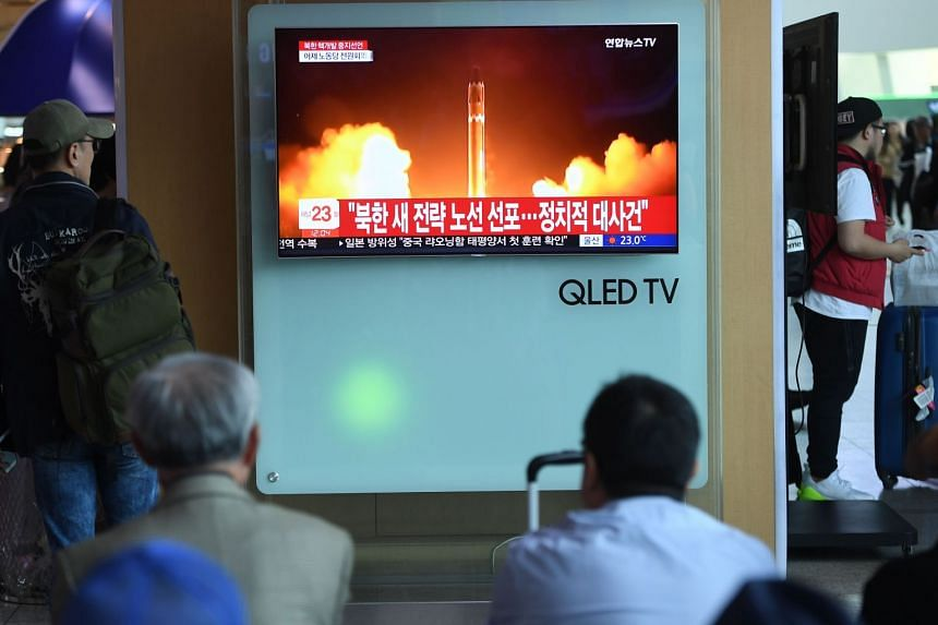People watching a file footage of a North Korean missile launch, at a railway station in Seoul on April 21, 2018.