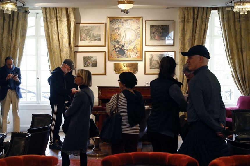 Visitors look at pieces of furniture prior to the auction.
