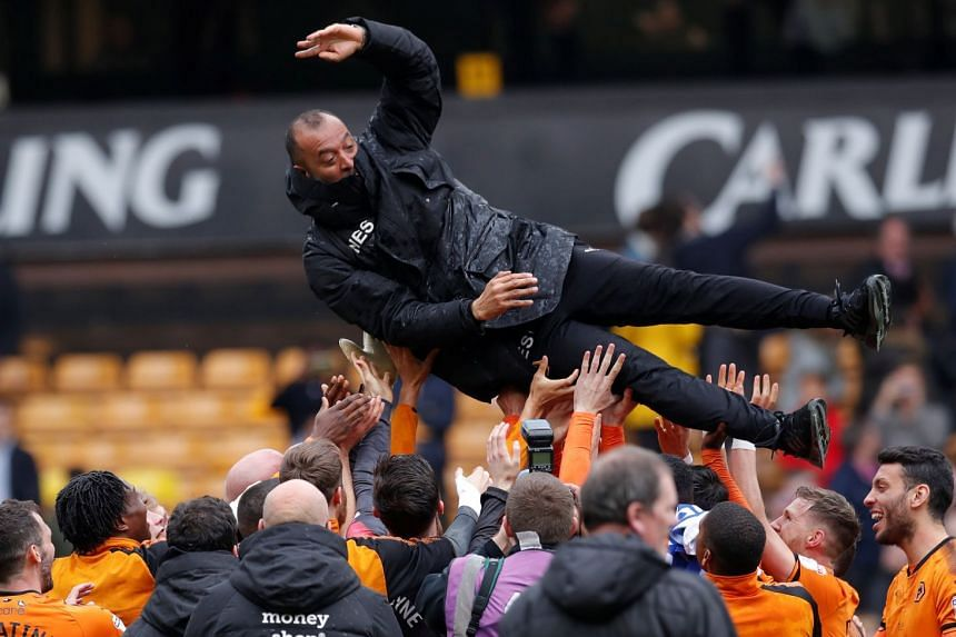 Wolves players throwing manager Nuno Espirito Santo as they celebrate promotion on April 15, 2018.