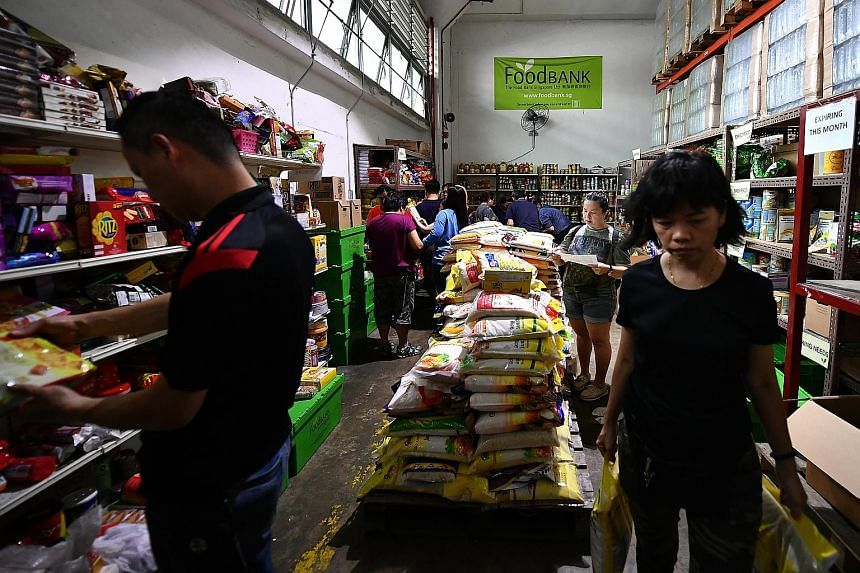 Left: Volunteers packing food items at Food Bank Singapore's warehouse in Tanjong Pagar Distripark. Above: Mr Heng Yam Chua, 70, a driver for the charity delivering pastries to a beneficiary last Tuesday.