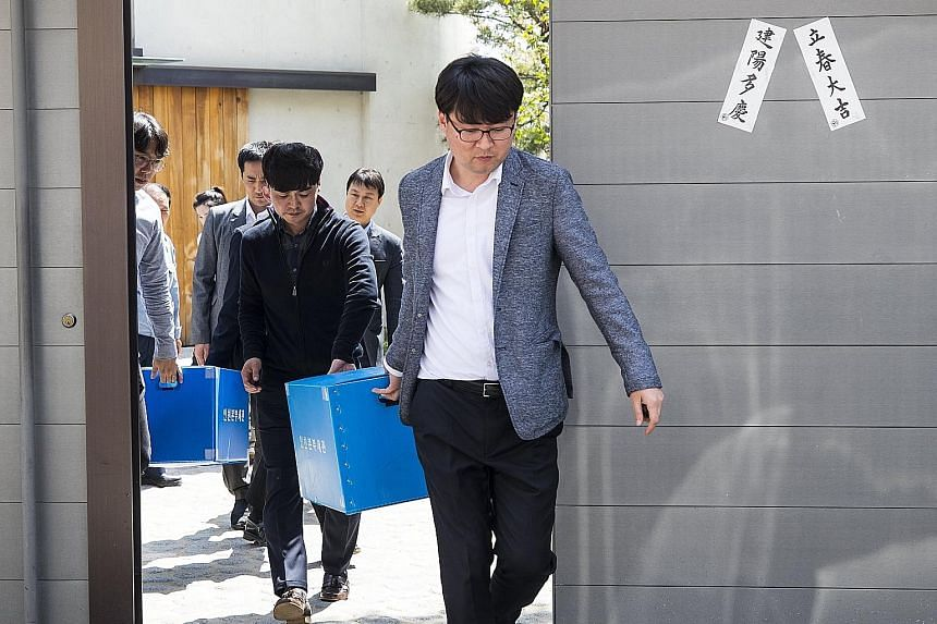 Customs investigators leaving Korean Air's main office in Seoul yesterday after a raid to search for evidence of smuggling.