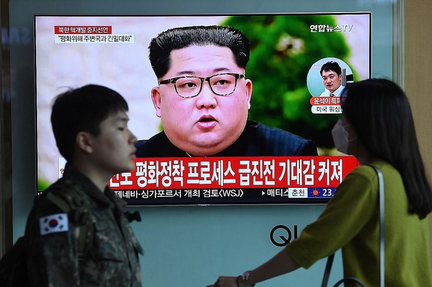 A TV screen at a railway station in Seoul yesterday showing file footage of North Korean leader Kim Jong Un. It was the second time in two days that Mr Kim made what appeared to be a significant concession to the United States, but in reality cemente
