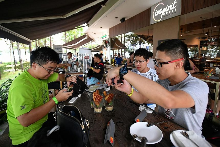From left: Lee Jia Hao, Desmond Lee and Ivan Lee taking photographs of their chendol dessert at Inspirit House at Punggol Settlement.
