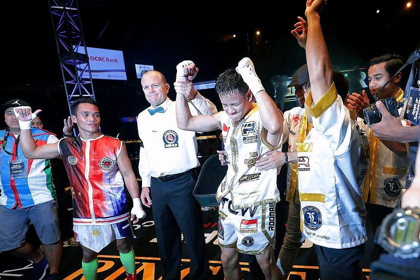 The referee raising Muhamad Ridhwan's hand as the winner after he scored a majority decision over Filipino Jeson Umbal at the Singapore Indoor Stadium on Friday night.