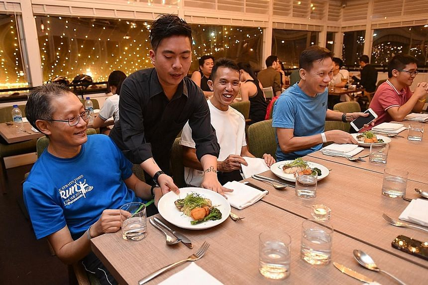 James Heng being served his order of seared sea bass with seaweed beurre blanc and grilled broccolini at The Summerhouse at Seletar Aerospace Park.
