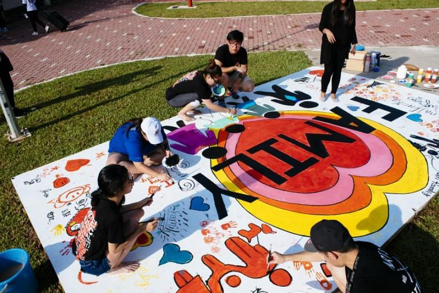 Participants painting a mural at a science-themed family camp held at the People's Association's Sembawang Water-Venture on April 22, 2018.