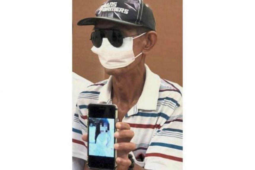 Mr Ong Chong Lim, who works as a part-time cleaner, holding up a photo of Angelina during the press conference at the Perak DAP headquarters.