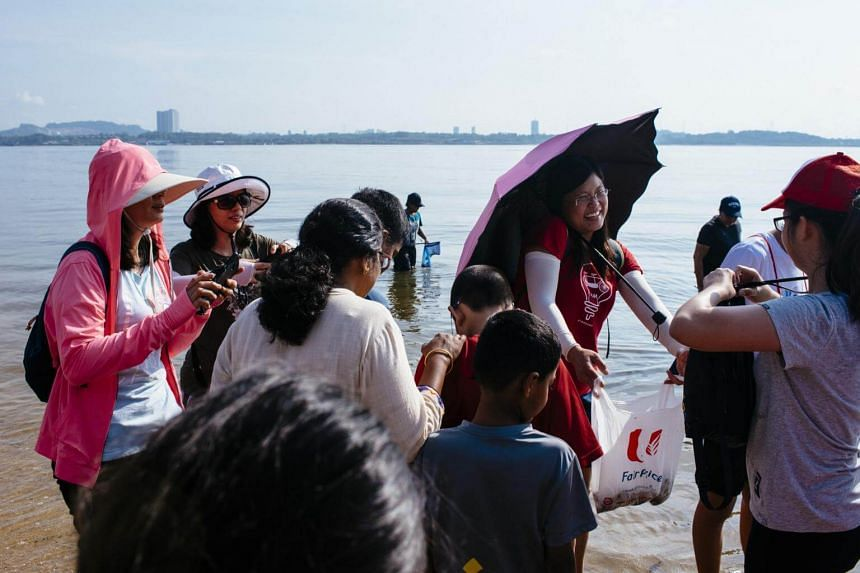 Housewife Chong Siaw Fen (with umbrella) showing participants a flower crab caught along the shore during an intertidal walk.