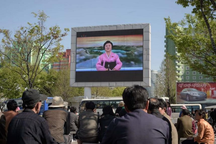 People watch a public television screen showing coverage of the 'Third Plenary Meeting' of the 7th central committee of the ruling Workers' Party, in Pyongyang on April 21, 2018.