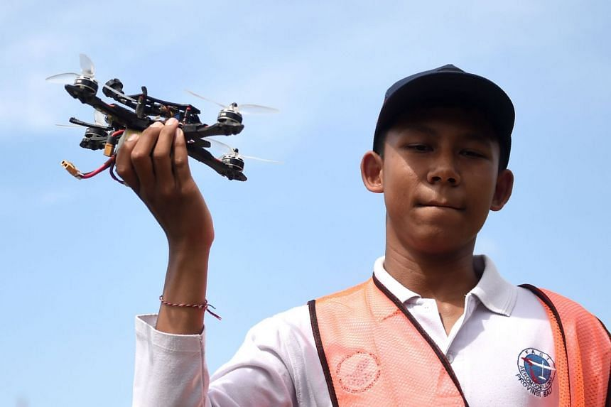 A man holding a drone during the FAI Drone Racing World Cup event in Denpasar, Bali on April 7, 2018.