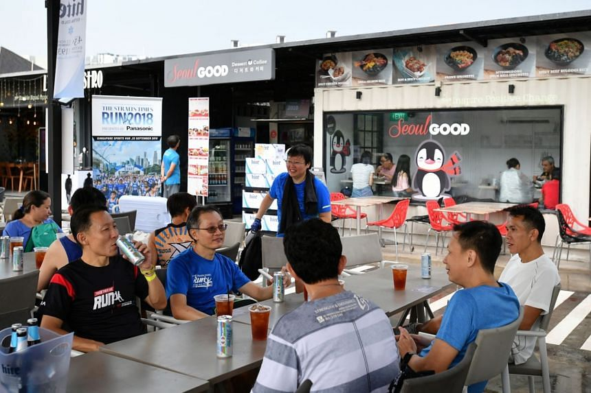 Participants having Korean fried chicken wings with iced tea at Seoul Good cafe at Tebing Lane, for the Eat And ride programme as part of The Straits Times Run 2018 buildup, on April 21, 2018.