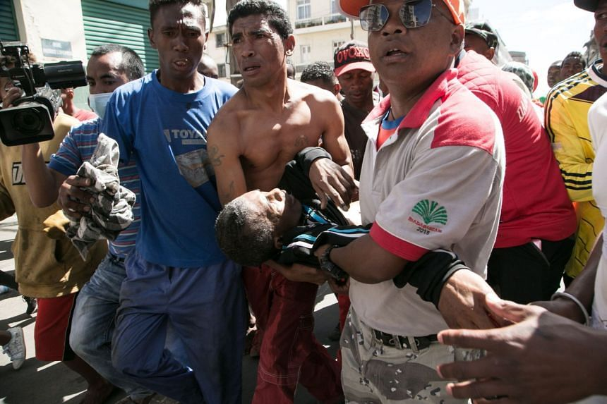 People carry a man shot in the abdomen during clashes with police in Antananarivo.