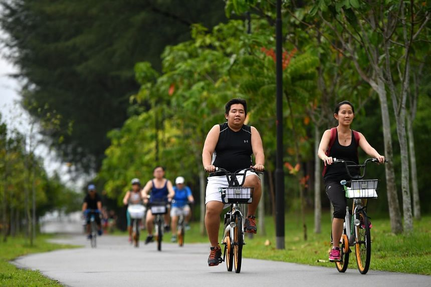 Mr Gary Lim, (left) 35, a chef; and Ms Sherlyn Lee, 39, a housekeeping manager, cycling towards Punggol Settlement.