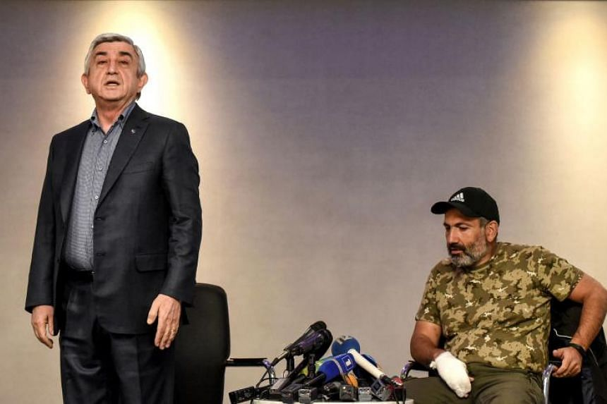 Armenian Prime Minister Serzh Sarkisian (left) standing up before leaving a televised meeting with anti-government protest leader Nikol Pashinyan, at a hotel in Yerevan on April 22, 2018.