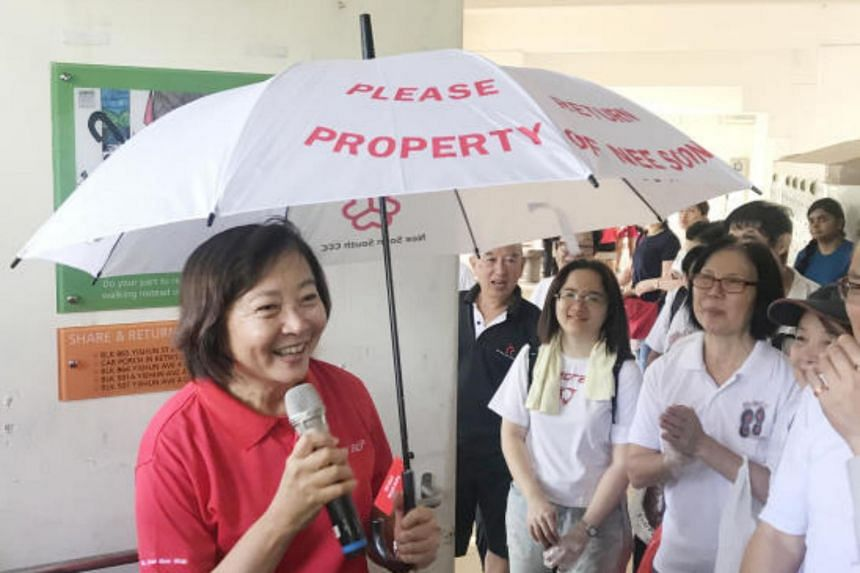 Nee Soon GRC MP Lee Bee Wah addressing residents while holding an umbrella from an umbrella-sharing initiative as part of an Earth Day event on April 22, 2018.