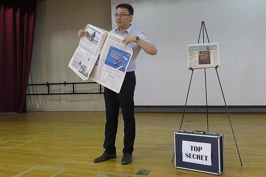 Mr Edwin Wan holding up a copy of The Straits Times as he unveils his predictions during a session in Yio Chu Kang Primary School last Wednesday. The head of the English language department hopes to motivate pupils to want to find out more about thin