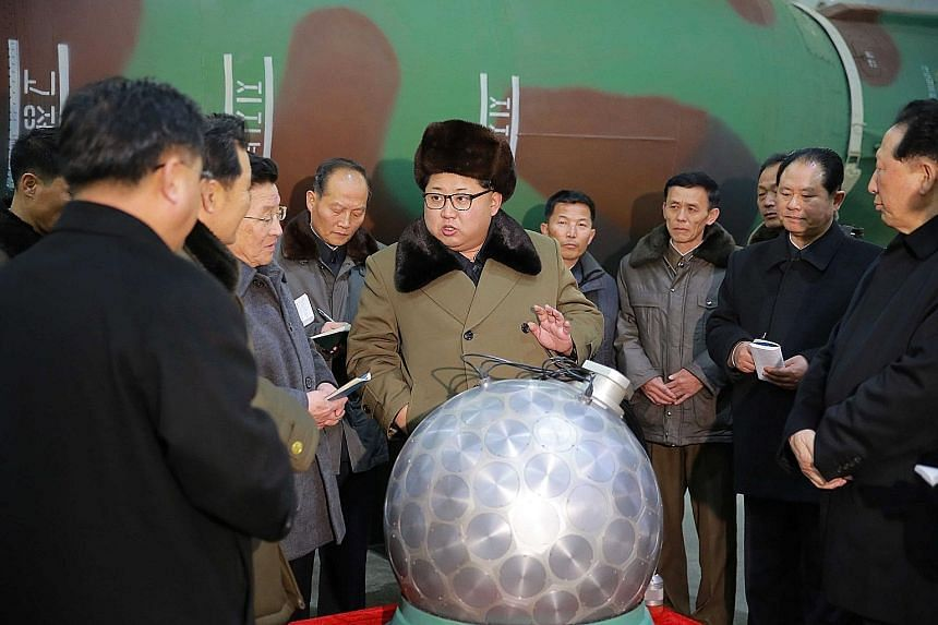 Above: An undated photo released by the Korean Central News Agency (KCNA), the state news agency of North Korea, showing North Korean leader Kim Jong Un (centre) talking with scientists and technicians involved in the research of nuclear weapons, at