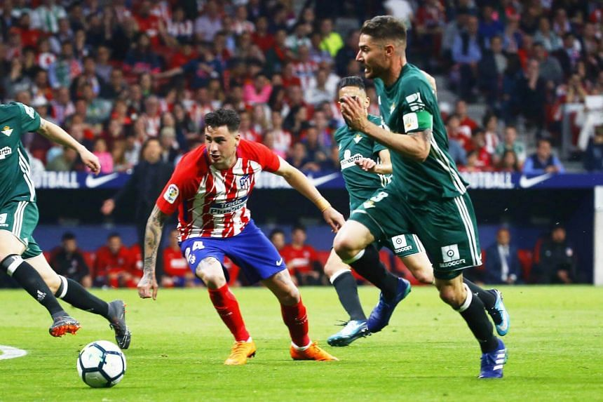 Atletico Madrid's defender Jose Maria Gimenez (left) in action against Betis' Javi Garcia during the match between Atletico Madrid and Real Betis at Wanda Metropolitano stadium in Madrid, Spain, on April 22, 2018.