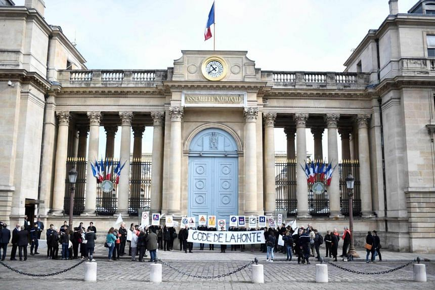 "People holding placards and a banner reading ""code of shame"" during a demonstration organised by a French organisation to promote the rights of migrants and refugees outside the French National Assembly in Paris on April 16, 2018."