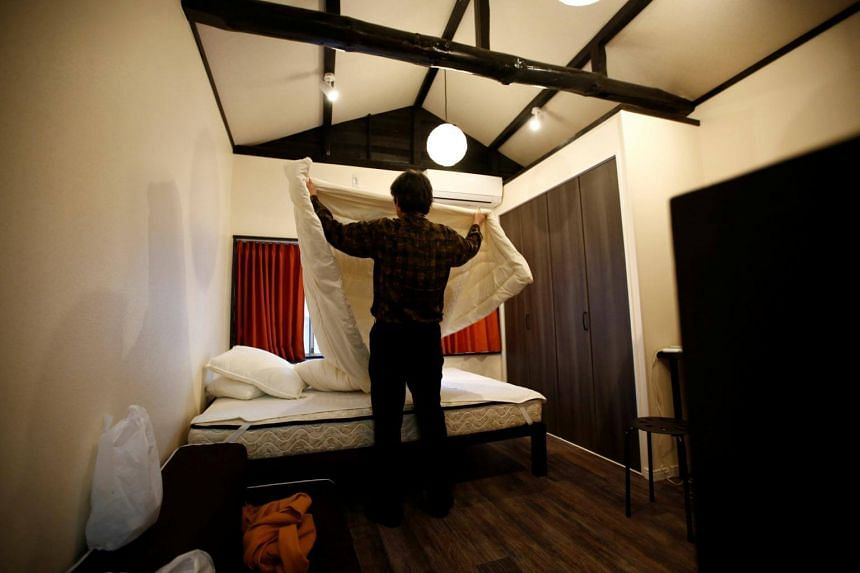 Mr Yasuhiro Inaoka arranges a bed after guests checked out at an apartment which is used as an Airbnb service in Tokyo, Japan, on March 12, 2018.