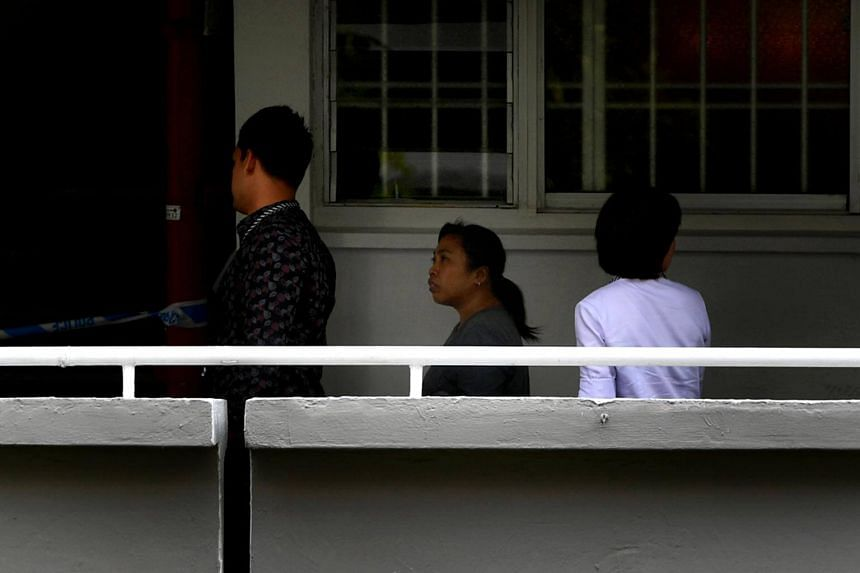 Indonesian maid Minah (centre) seen leaving the unit at Tampines Street 22 with police officers, on Feb 13, 2017, to assist in investigations.