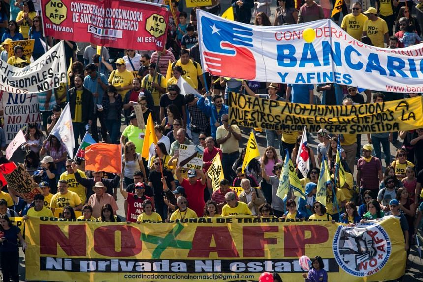 Waving banners, chanting noisy slogans to the sound of trumpets and drums, pensioners and workers with their families marched through Santiago demanding an end to the current system, known by its Spanish acronym AFP.