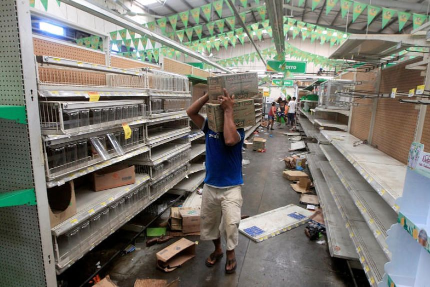 People with goods looted from a store are seen after a protest over a controversial reform to the pension plans of the Nicaraguan Social Security Institute (INSS) in Managua, Nicaragua April 22, 2018.