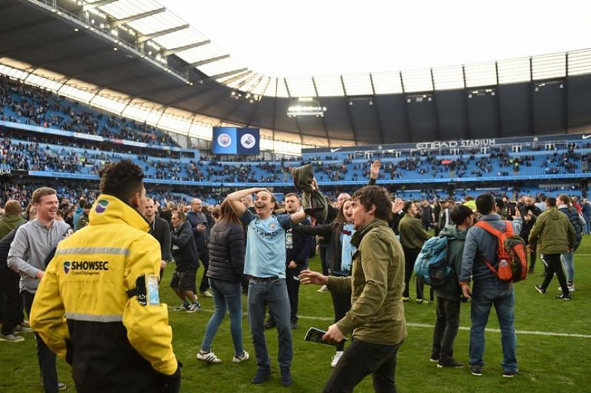 Fans invade the pitch at the end of the English Premier League football match between Manchester City and Swansea City at the Etihad Stadium in Manchester, north west England, on April 22, 2018.