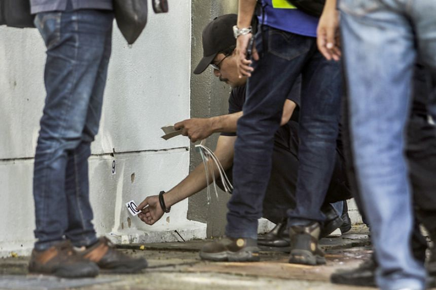 Royal Malaysian Police forensic officers collect evidence at the crime scene where Palestinian scientist Fadi al-Batsh was reportedly assassinated in a drive-by motorcycle shooting in Kuala Lumpur on April 21, 2018.