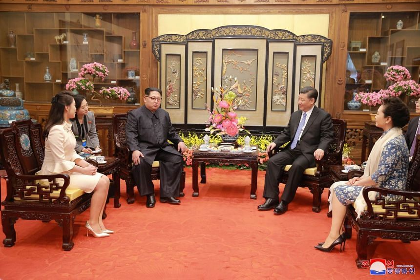 North Korean leader Kim Jong Un and wife Ri Sol Ju, meeting Chinese President Xi Jinping and wife Peng Liyuan, in this undated photo released by North Korea's Korean Central News Agency (KCNA), on March 28, 2018.