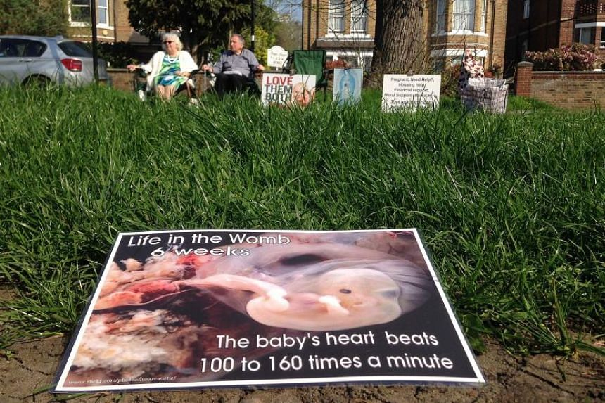 Colleen Wallace (left) and Eamonn Gill (right), who oppose abortion attend a pro-life vigil on the street outside the Marie Stopes clinic, which offers contraception and abortion services, in London on April 21, 2018.