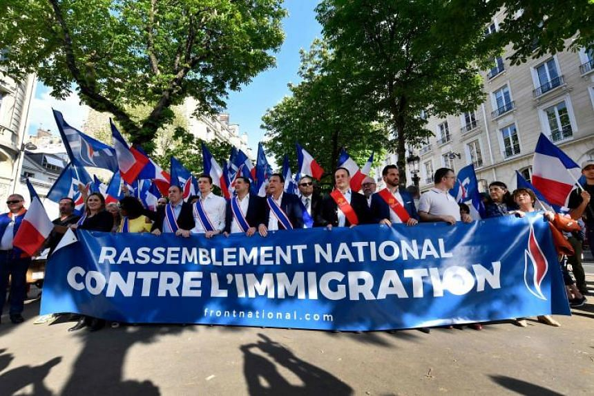 Supporters and elected officials of the French far-right Front National party hold a banner during a rally against the French government's immigration policies next to the National Assembly in Paris on April 20, 2018.