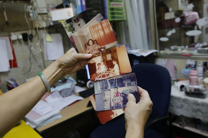 Ms Wong Siew Lin holding up photos of her four children playing in the office of her workshop.