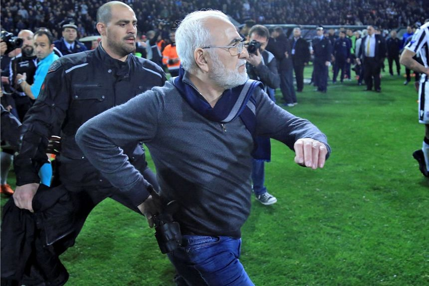 Ivan Savvides, Russian-born Greek businessman and owner of Paok Salonika, with what appears to be a gun in a holster, entering the pitch after the referee annulled a goal during their match against AEK Athens on March 11, 2018.