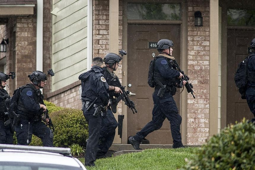 A Swat team and bomb squad set to enter the apartment building of suspected gunman Travis Reinking (above) who opened fire with an assault rifle at a Waffle House Restaurant in Nashville, Tennessee, early on Sunday. He is still at large.