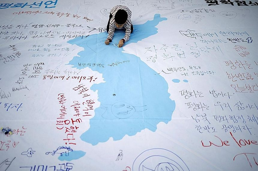 A child writing a message on a unification flag wishing for a successful inter-Korean summit during a rally in central Seoul, South Korea, last Saturday.