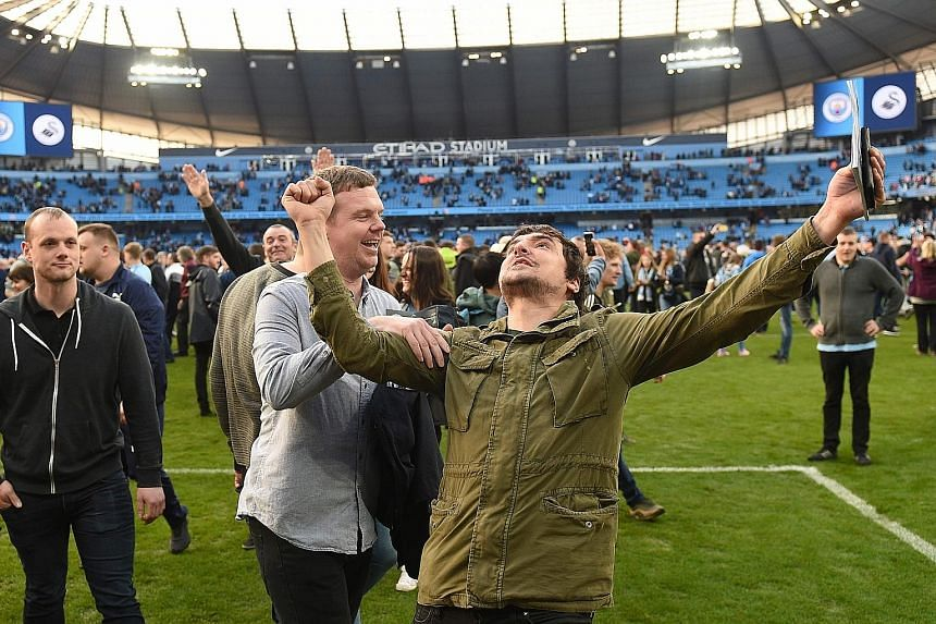 An exuberant Manchester City fan celebrating on the Etihad Stadium pitch after the 5-0 Premier League win over Swansea. The Football Association is investigating the pitch invasion but City manager Pep Guardiola is relaxed about the prospect of a pen