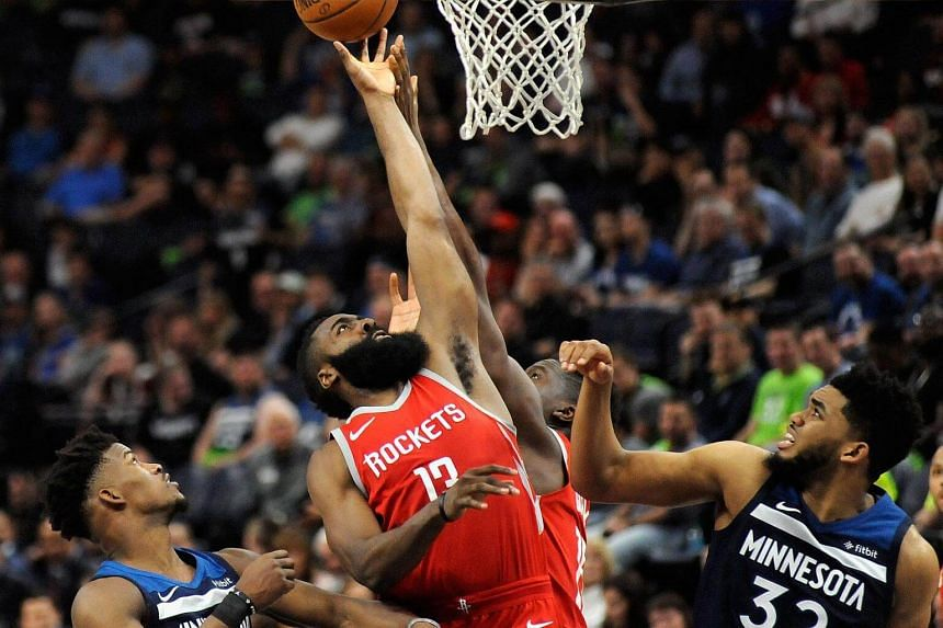 The Houston Rockets' James Harden tips the ball against the Minnesota Timberwolves' Jimmy Butler and Karl-Anthony Towns during their first-round game of the 2018 NBA Playoffs at the Target Center in Minneapolis on April 23, 2018.