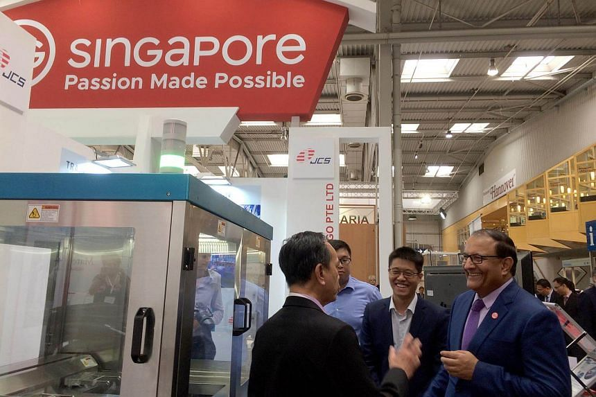 Minister for Trade and Industry (Industry) S. Iswaran (in purple tie) dropping in on Singapore companies which have set up booths under the Singapore Pavilion at the Hannover Messe trade fair.