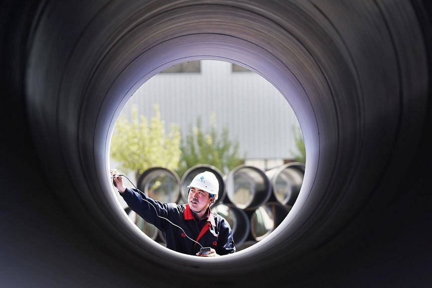 A worker measures a steel pipe at a factory in Zouping in China's eastern Shandong province on April 18, 2018.