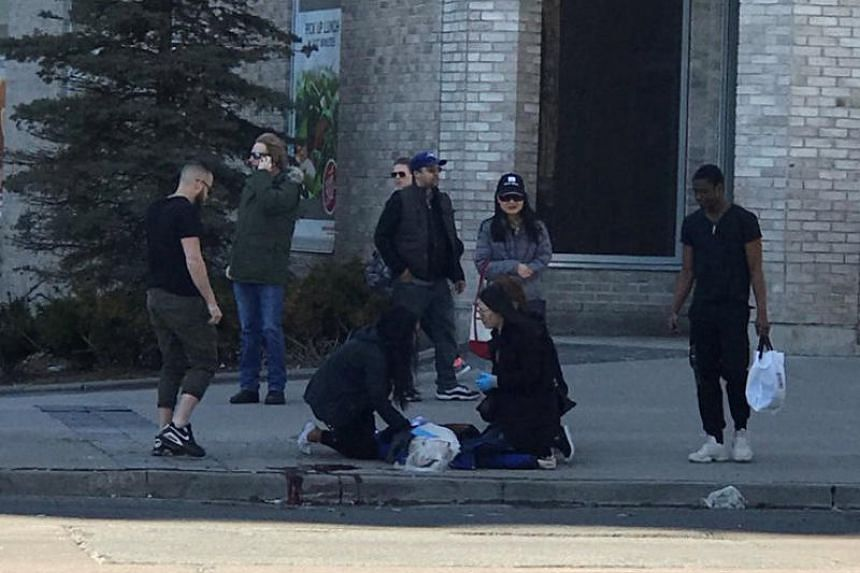 A victim is helped by pedestrians after a van hit multiple people at a major intersection in Toronto on April 23, 2018.