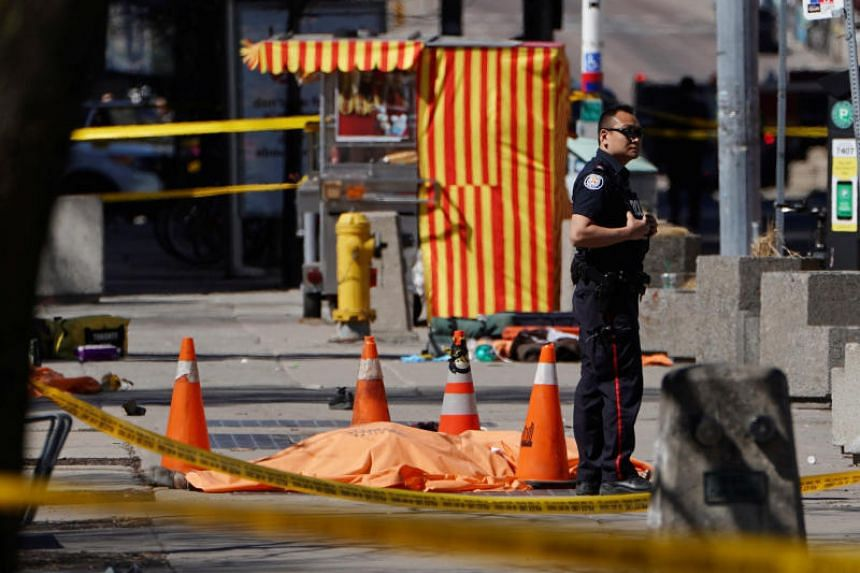 A police officer standing next to a victim of an incident where a van struck multiple people at a major intersection in Toronto's northern suburbs on April 23, 2018.