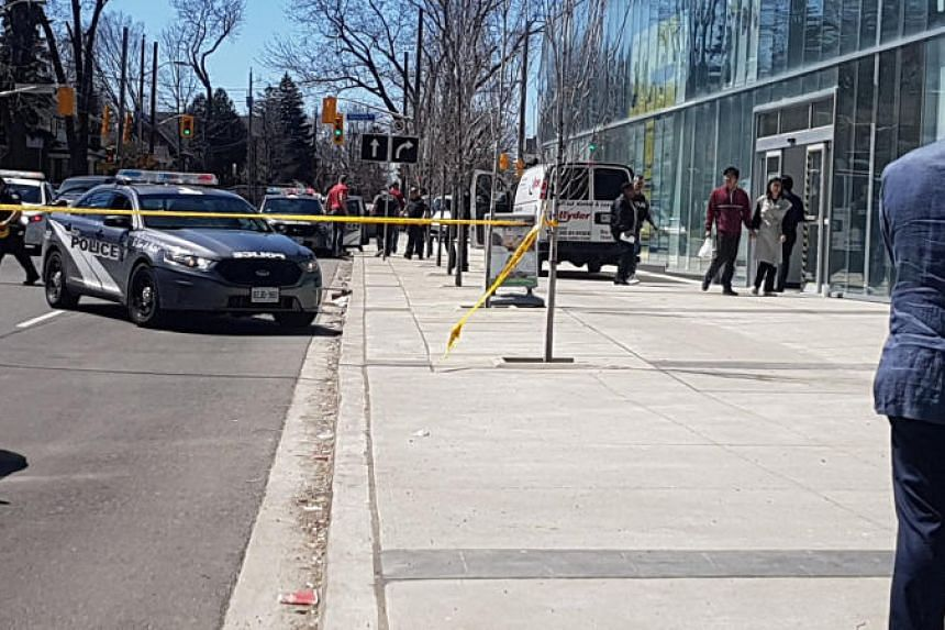 Police officers arrest the suspect driver after a van hit multiple people at a major intersection in Toronto on April 23, 2018, in this picture obtained from social media.
