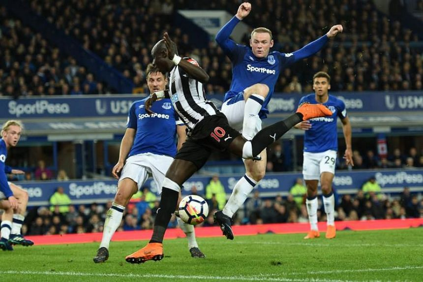 Everton's English striker Wayne Rooney (right) collides with Newcastle United's Senegalese midfielder Mohamed Diame to concede a corner during the EPL match between Everton and Newcastle United at Goodison Park in Liverpool, north west England on Apr