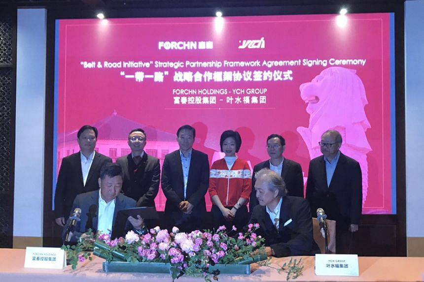 Senior Minister of State for Trade and Industry Sim Ann (standing, third from right) witnesses the signing of a deal between YCH Group and Forchn Holdings on April 24, 2018.