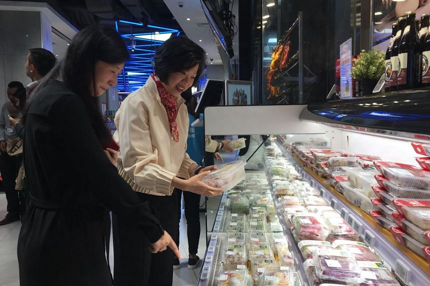 Senior Minister of State for Trade and Industry Sim Ann (right) at one of Alibaba's Hema supermarkets in downtown Shanghai.