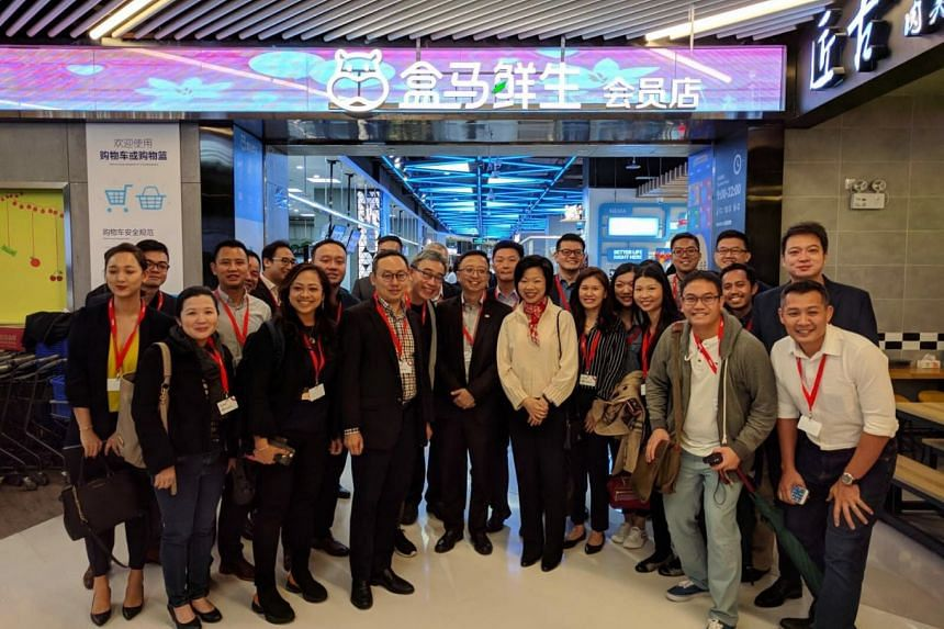 The Singapore business delegation, led by Senior Minister of State for Trade and Industry Sim Ann, visited e-commerce giant Alibaba's Hema supermarket in downtown Shanghai.