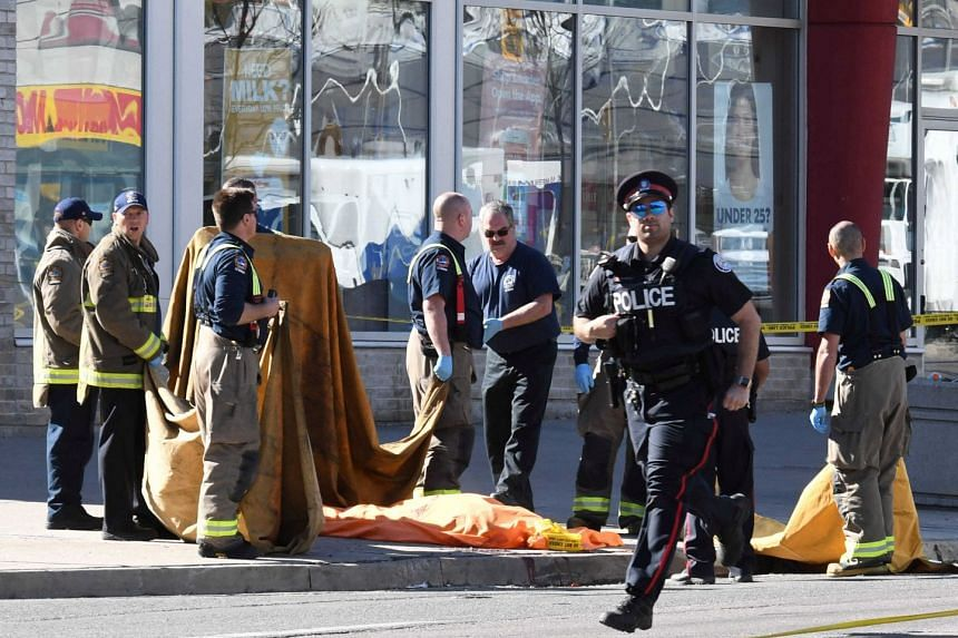 Firefighters stand near a covered body after a van struck multiple people at a major intersection northern Toronto, Ontario, Canada, on April 23, 2018.